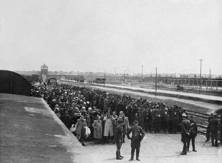 Před selekcí na rampě v Osvětimi-Birkenau, v pozadí je vidět táborová brána, kterou všechny vlaky přijížděly, Foto: Židovské muzeum v Praze