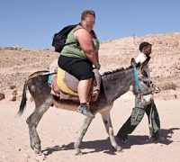 Shows: Overwight tourist on donkey - non PIXELATED LifeÛs no beach for holiday donkeys. UK charity, the Brooke, reveals shock footage and publishes code to stop animals paying the price for cheap rides and tubby tourists    Shocking pictures and video footage by the Brooke, from popular British tourist destinations including the Pyramids of Giza and the Ancient City of Petra, show that many tourists disregard the welfare of animals as they have fun in the sun. While British beach donkeys prepare for their regulated day job - no passengers over eight stone, annual health checks, a day off each week and a one hour lunch break - overseas itÛs a different story. Bigger Brits and bargain hunters bring daily suffering to horses and donkeys who taxi tourists - on their back or in a heavy carriage - across tricky terrain in the blazing sun. No weight restrictions apply and the bigger the tourist the harder it gets. Recorded incidents include two women giggling on a tiny donkey as it descends a perilous path, travellers urging owners to race painfully thin carriage horses while they whip them with electric flex and heavy holidaymakers relaxing on donkeysÛ backs as they scale 900 steps for the third time that day*.  RE Lucy Ballinger story