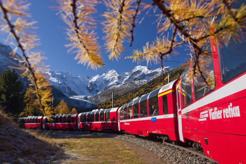 ENGADIN St. Moritz - Rhaetian Railway at the Montebello Curve, surrounded by golden larch trees. In the background, the Morteratsch Glacier, Bellavista (3,922m), Crast'Aguezza (3,854m), Piz Bernina (4,049m), Piz Prievlus (3,610m) and Piz Morteratsch (3,751m).  Copyright by ENGADIN St. Moritz By-line:swiss-image.ch/Christof Sonderegger